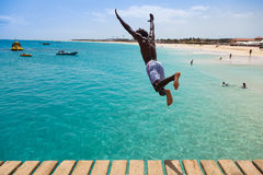 Muchacho caboverdiano adolescente que salta en el agua de la turquesa de Sant Foto de archivo