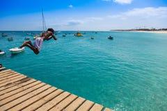 Muchacho caboverdiano adolescente que salta en el agua de la turquesa de Sant Fotografía de archivo libre de regalías
