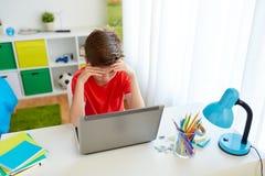 Muchacho cansado del estudiante con el ordenador portátil en casa Foto de archivo