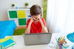 Muchacho cansado del estudiante con el ordenador portátil en casa Fotos de archivo