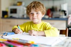 Muchacho cansado del niño en casa que hace letras de la escritura de la preparación con las plumas coloridas Fotografía de archivo libre de regalías
