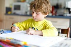 Muchacho cansado del niño en casa que hace letras de la escritura de la preparación con las plumas coloridas Fotografía de archivo