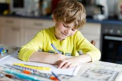 Muchacho cansado del niño en casa que hace letras de la escritura de la preparación con las plumas coloridas Foto de archivo