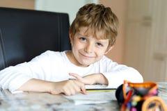Muchacho cansado del niño en casa que hace letras de la escritura de la preparación con las plumas coloridas Imagenes de archivo