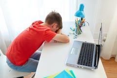 Muchacho cansado o triste del estudiante con el ordenador portátil en casa Foto de archivo libre de regalías
