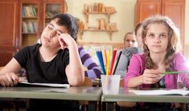 Muchacho cansado que duerme durante la lección en la escuela Imagen de archivo