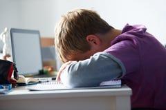 Muchacho cansado que estudia en dormitorio Fotos de archivo