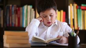 Muchacho cansado que lee en casa almacen de video
