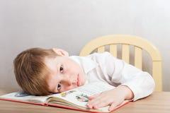 Muchacho cansado triste en la camisa blanca que se sienta en el escritorio imagenes de archivo