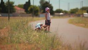 Muchacho cansado y muchacha que hacen autostop en el camino almacen de metraje de vídeo
