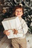 Muchacho caucásico del niño joven que lleva a cabo el regalo de Navidad en Front Of Christmas Tree Muchacho sonriente feliz lindo imagen de archivo