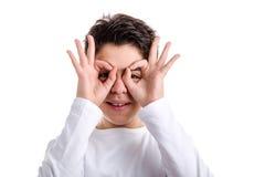 Muchacho caucásico feliz con la piel del acné usando las manos como máscara Imagen de archivo