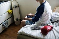 Muchacho caucásico joven que celebra el control del juego que se sienta en cama Foto de archivo libre de regalías