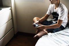 Muchacho caucásico joven que celebra el control del juego que se sienta en cama Imágenes de archivo libres de regalías