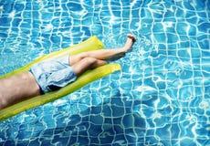 Muchacho caucásico joven que disfruta de la flotación en la piscina foto de archivo libre de regalías