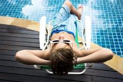 Muchacho caucásico joven que disfruta de tomar el sol por la piscina Foto de archivo libre de regalías