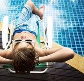 Muchacho caucásico joven que disfruta de tomar el sol por la piscina Imagen de archivo