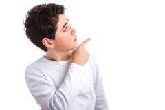 muchacho caucásico Liso-pelado que señala hasta su izquierda con la derecha Foto de archivo