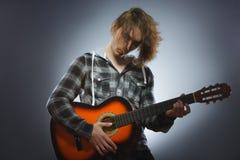 Muchacho caucásico que juega en la guitarra acústica Adolescente con la guitarra de madera clásica Foto de archivo libre de regalías