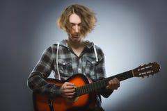 Muchacho caucásico que juega en la guitarra acústica Adolescente con la guitarra de madera clásica Foto de archivo