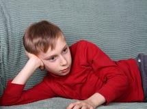 Muchacho caucásico rubio encantador en la mentira roja en el pensamiento verde del sofá Imagen de archivo