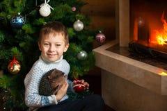 Muchacho cerca de la chimenea y del árbol de navidad Imagenes de archivo