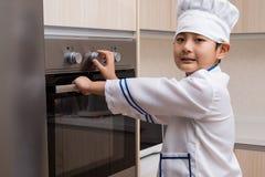 Muchacho chino asiático en las galletas blancas de la hornada del uniforme del cocinero fotos de archivo