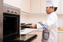 Muchacho chino asiático en las galletas blancas de la hornada del uniforme del cocinero imágenes de archivo libres de regalías