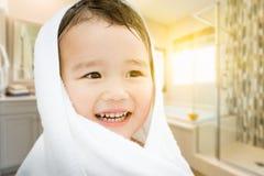Muchacho chino y caucásico de la raza mixta linda feliz en abrigo del cuarto de baño imagenes de archivo