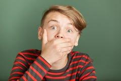 Muchacho chocado cubriendo su boca Imagen de archivo libre de regalías