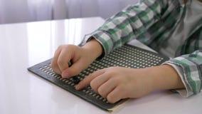 Muchacho con deficiencias visuales del niño que aprende escribir la fuente de caracteres Braille que se sienta en la tabla en el  almacen de metraje de vídeo