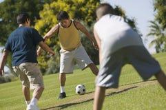 Muchacho (13-15) con dos hombres jovenes que juegan a fútbol al aire libre en parque. Fotos de archivo libres de regalías