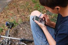 Muchacho con el artilugio cerca de la bici Imagen de archivo libre de regalías