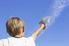Muchacho con el avión de papel contra el cielo azul Opinión de ángulo bajo Imagenes de archivo