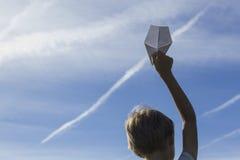 Muchacho con el avión de papel en su mano contra el cielo azul Opinión de ángulo bajo Imagen de archivo libre de regalías