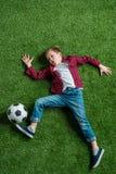 Muchacho con el balón de fútbol que miente en hierba verde fotos de archivo