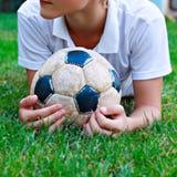 Muchacho con el balón de fútbol viejo Fotos de archivo