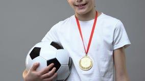 Muchacho con el balón de fútbol y primera situación de la medalla del lugar contra fondo gris metrajes