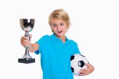 Muchacho con el balón de fútbol y taza delante del fondo blanco Imagen de archivo