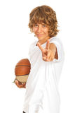 Muchacho con el baloncesto que muestra la victoria Imagenes de archivo
