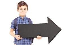 Muchacho con el bolso de escuela que sostiene una flecha negra grande que señala a la derecha Imágenes de archivo libres de regalías
