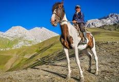 Muchacho con el caballo en Kirguistán fotos de archivo