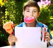 muchacho con el caramelo y la hoja de papel de algodón Foto de archivo libre de regalías