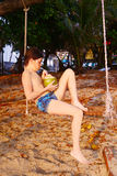 Muchacho con el coco en el oscilación de la playa Imagen de archivo
