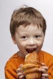 Muchacho con el croissant imagen de archivo libre de regalías