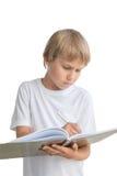 Muchacho con el cuaderno y la escritura de la pluma algo, aislado en el fondo blanco Fotografía de archivo libre de regalías