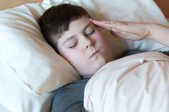 Muchacho con el dolor de cabeza que miente en cama Fotografía de archivo