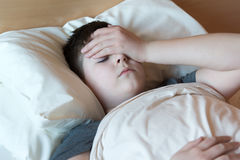 Muchacho con el dolor de cabeza que miente en cama Imagen de archivo