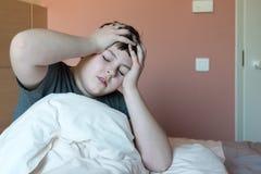 Muchacho con el dolor de cabeza que se sienta en cama Imagen de archivo libre de regalías