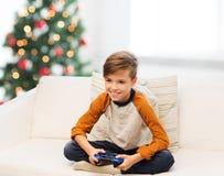 Muchacho con el gamepad que juega al videojuego en la Navidad Imagen de archivo libre de regalías